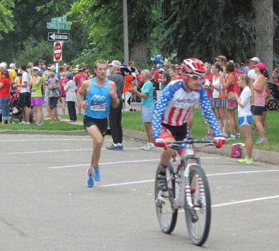 Cyclist riding in front of the leader of the 2014 FireKracker 5k Elite Race.